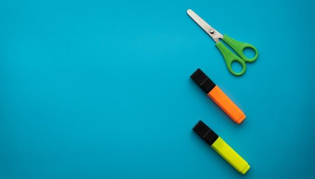 Ножницы и цветные маркеры, изолированные на синем фоне. школьные принадлежности. концепция образования. скопируйте пространство.