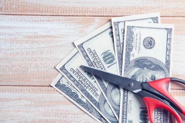 테이블에 가위와 달러 지폐