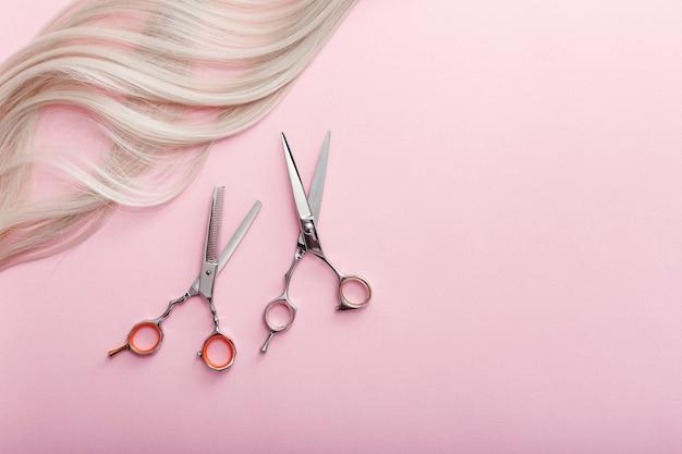 はさみや他の美容師のアクセサリーとピンクの背景にブロンドの髪のストランド。美容サービス。