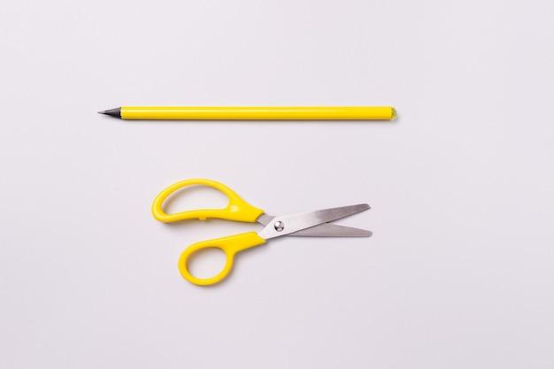 Ножницы и карандаш на белом фоне. материалы для подготовки к оформлению праздника.