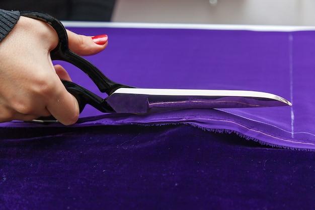Ножницы и фиолетовый текстиль. крупным планом фото, если женская рука ножницами разрезает фиолетовую ткань.