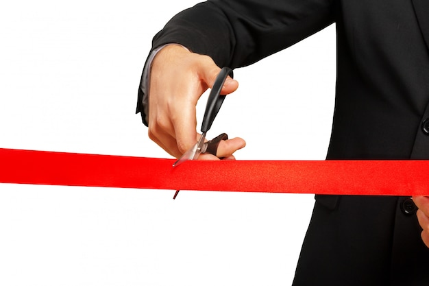 Scissors are cutting red ribbon or tape. isolated on white .
