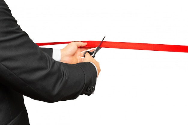Scissors are cutting red ribbon or tape