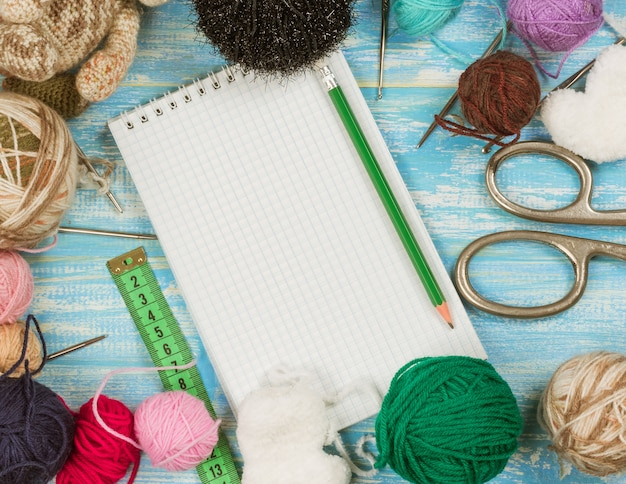 Scissors, balls of wool, measuring tape and notebook on a wooden table.