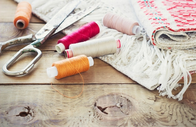 Scissors, bobbins with thread and needles, striped fabric. old sewing tools on the old wooden