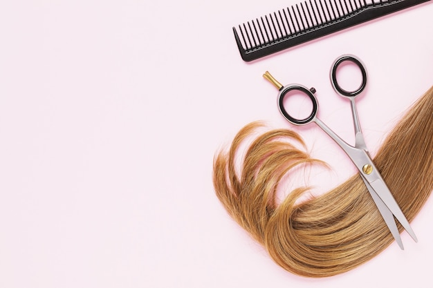 Scissors a comb and a cut strand of light colored female childrens hair with copy space on a pink background