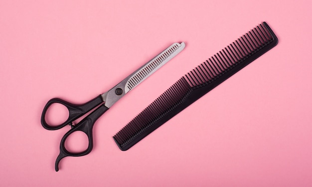 Scissors and comb on a pink background