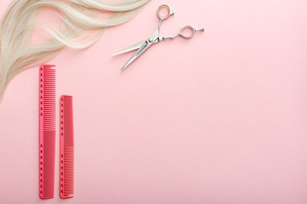はさみ、くし、その他の美容師のアクセサリーとピンクの背景にブロンドの髪のストランド。