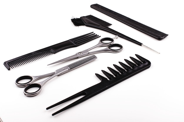 Scissors and combs for hair cut and treatment lie on a white table