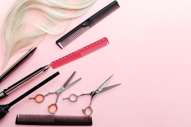 はさみ、くし、ヘアアイロン、その他の美容師のアクセサリー、ピンクの背景にブロンドの髪の毛。美容サービス。