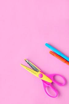 Ножницы мелки на розовом вертикальном фоне творческое школьное рабочее пространство с желтыми принадлежностями