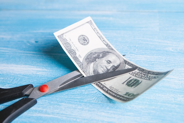 Scissors cut a dollar bill in half