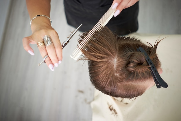 Scissors cut the girls hair in beauty salon, redhead woman.