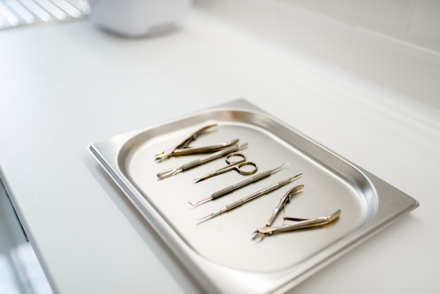 Ножницы, фрезы, маникюрное и педикюрное оборудование на металлической подносе, инструменты косметолога.