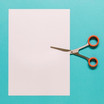Scissors cutting paper on blue background