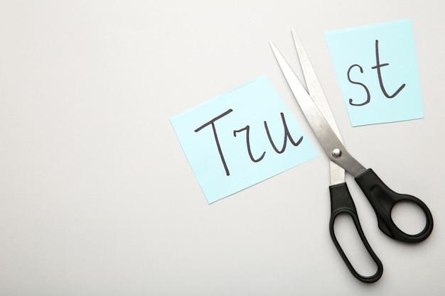 Ножницы для резки бумаги со словом доверие на серой поверхности