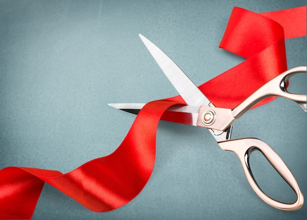 Scissors cutting red ribbon, close-up view on blue background