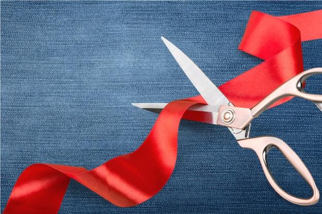 赤いリボンを切るはさみ、青い背景のクローズアップビュー