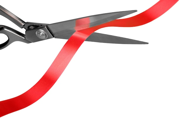 Scissors cutting red ribbon, close-up view on white background
