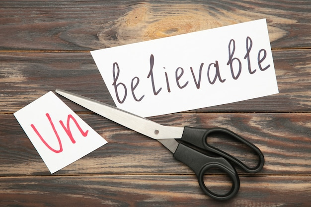 Scissors cutting white paper with the text unbelievable, change word to believable.