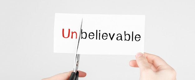 Scissors cutting white paper with the text unbelivable, change word to belivable.