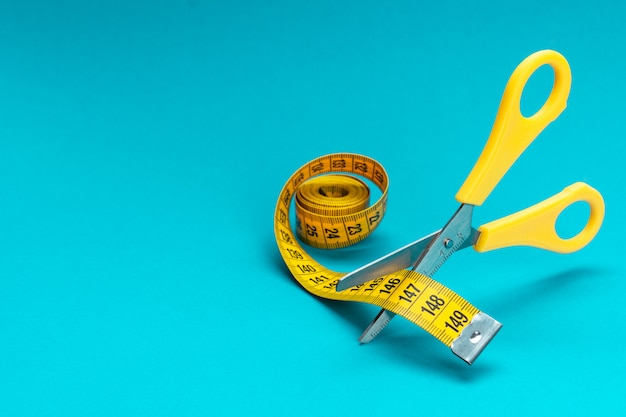 Scissors cutting yellow measuring tape dieting concept