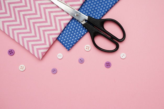 Scissors, fabrics and buttons for sewing with copy space