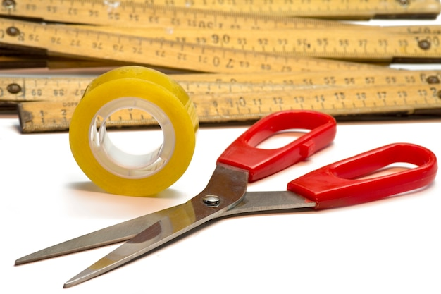 Scissors, folding rule and adhesive tape