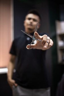 Scissors in hands on a background of blurry barber in a beauty salon