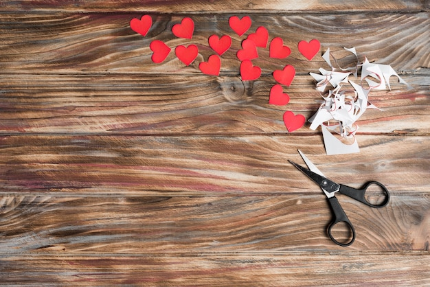Scissors and hearts on lumber background
