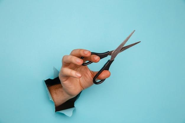 青い紙の破れた穴から手にハサミ