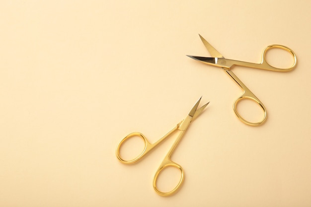 Scissors for manicure woman nails on beige background with copy space