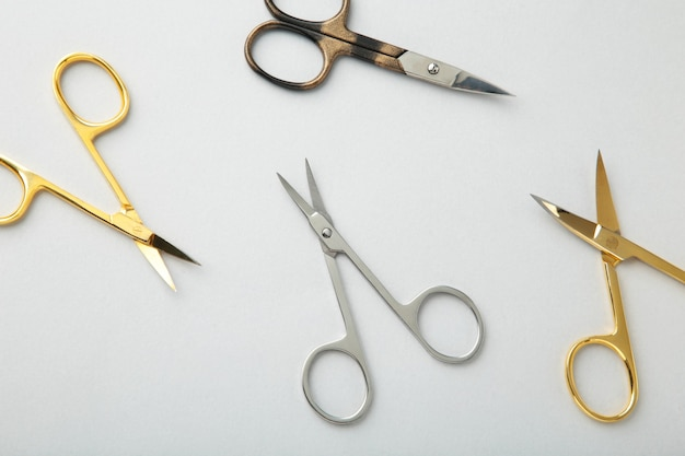 Scissors for manicure woman nails on grey surface