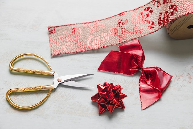 Scissors near red bows and christmas ribbon