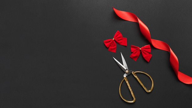 Scissors near red bows and ribbon