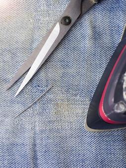 Ножницы, иголка с ниткой и утюг на рваной джинсовой ткани. ремонт джинсов в домашних условиях. вид сверху.