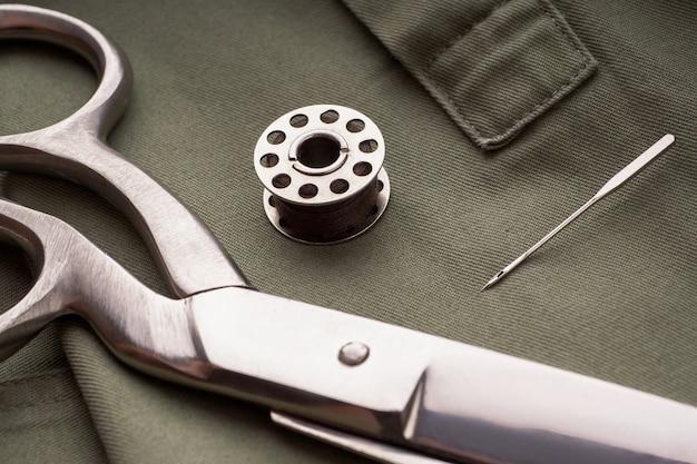 はさみ、針、糸のスプール、ラスパリーヴァテルが縫い付けられたシャツ、クローズアップに配置されています。テーラーまたはファッションデザイナーのデスク。洋服の縫製、アクセサリーのコンセプトの縫製。ファッションデザインの要素。