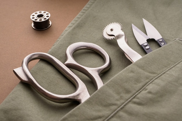 Scissors, needles, spools of thread, a rasparyvatel are laid out on a sewn shirt, close-up. tailor's or fashion designer's desk. sewing clothes, sewing accessories concept. fashion design elements.