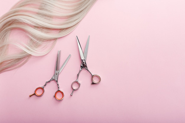 Scissors and other hairdresser's accessories and strand of blonde hair on pink background. hairdresser service.