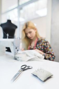 Scissors and pillow with needles on the background of seamstresses working in the workplace