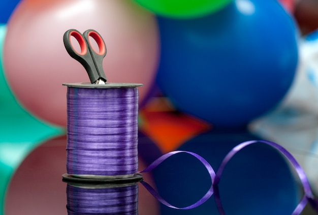 Scissors and purple washi tape at blurred multicolored balloons background.