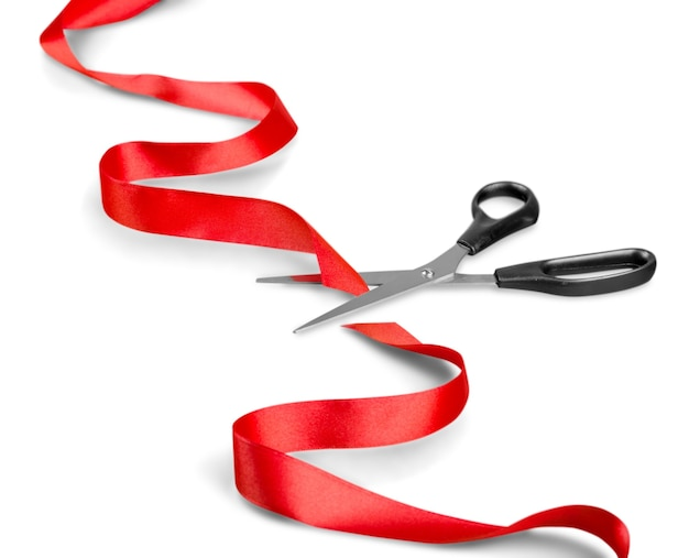 Scissors and red ribbon on a white background