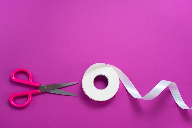Scissors and a roll of tape white on a purple background.