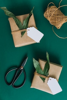 Scissors; spool and two gift boxes on green background