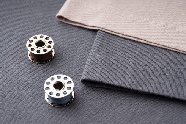 はさみ、糸のスプール、針、センチメートルがtシャツの濃い灰色の生地の上にあります。縫製服の背景にアクセサリーを縫います。裁断と縫製のコンセプト。テーラーズデスク。