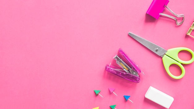Scissors; stapler; bulldog clip; eraser and push pins on pink background