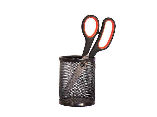 Ножницы с красной ручкой в черном металлическом держателе. изолировать