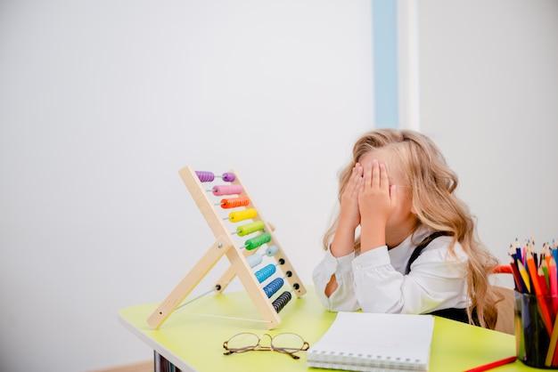 クレヨンでテーブルに触発された少女。学用品、鉛筆、バッグ、scketchbook、そろばんを備えたスクールデスク。眼鏡をかけて学校概念に戻って小さなブロンドの女の子。