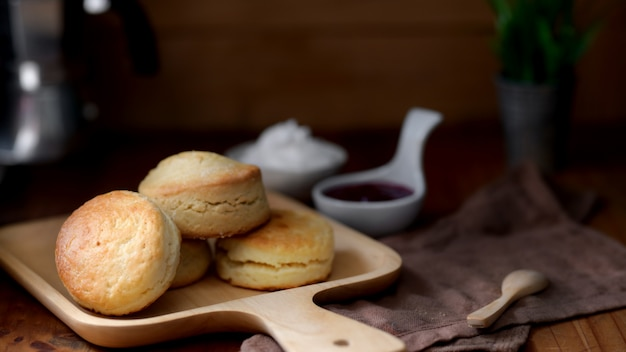 Scones on wooden tray with strawberry jam and clotted cream