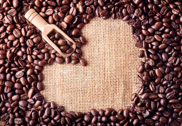 Scoop on coffee beans arranged as a heart shape on bag background